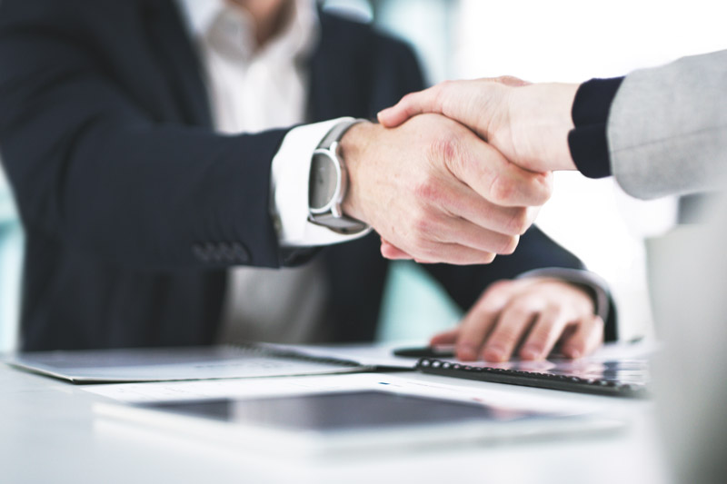 Businesspeople shake hands over a table with paperwork on it